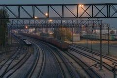 Illuminated cargo train station by night Stock Photos
