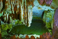 Illuminated Cave Landscape with water, Ha Long Bay, Vietnam Royalty Free Stock Image