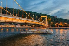 Buda Castle and the Danube. The illuminated Chain Bridge across the  Danube River at the beginning of the night Royalty Free Stock Images