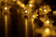 Illuminated chain of starry lights in festive atmosphere Royalty Free Stock Photos