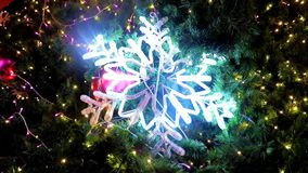 Illuminated Christmas decoration on the tree. Illuminated Christmas decoration snowflake on the tree stock footage
