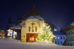 Illuminated Christmas fir tree in front of the church in Gruyere Stock Images