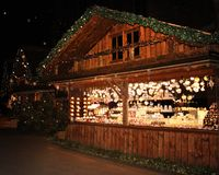 Illuminated Christmas market fair kiosk. Sale of mulled wine, Christmas trees and gingerbread stock photos