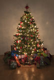 Illuminated christmas tree with presents royalty free stock image