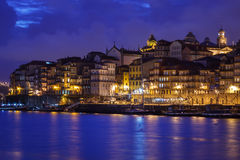Illuminated city buildings and boats reflecting colorful lights into Douro River along waterfront in Porto, Portugal. Illuminated city buildings and boats Royalty Free Stock Images