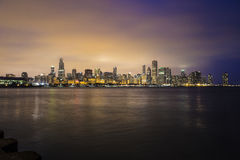 Illuminated city skyline along waterfront Royalty Free Stock Image