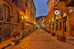 Illuminated cobbled street with light reflections on cobblestones in old historical city by night. Dark blurred. Silhouette of person evokes Jack the Ripper Royalty Free Stock Photos
