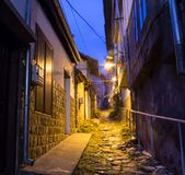Illuminated cobbled street with light reflections on cobblestones in old historical city by night. Dark blurred. Silhouette of person evokes Jack the Ripper Stock Image