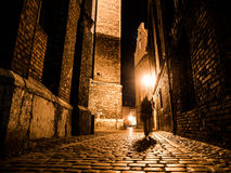 Illuminated cobbled street in old city by night Stock Photos
