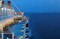 Illuminated cruise ship with people in sea Stock Photo