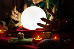Illuminated crystal ball and hands of fortune teller woman Royalty Free Stock Images