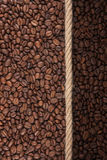 Illuminated and dark coffee beans and rope Royalty Free Stock Photos