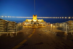 Illuminated deck of cruise ship at evening. Bar and tables in center of image Royalty Free Stock Photos