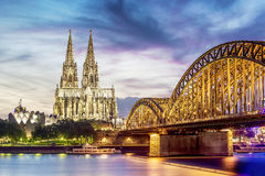 Illuminated Dom in Cologne. With bridge and rhine at sunset Stock Image