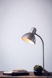 Illuminated electric lamp by books on table Stock Photography