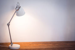 Illuminated electric lamp on wooden table Royalty Free Stock Image