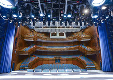 Illuminated empty concert stage. View from the illuminated empty concert stage to the lit auditorium Royalty Free Stock Photography