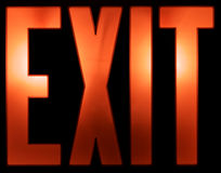 Illuminated EXIT Sign on Black Stock Photography