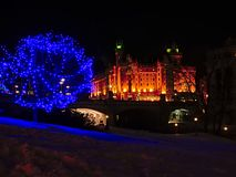Illuminated Fairmont Château Laurier castle at night on a winter day with snow in Ottawa, capital of Canada. Seen from Major`s hill park with bare trees stock photography