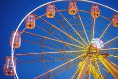 Illuminated ferris wheel in amusement park at a night city