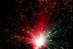 Illuminated Fiber Optic Strands on Black. Close up Ends of Many Illuminated Red and Green Fiber Optic Strands on Black Background Stock Photo