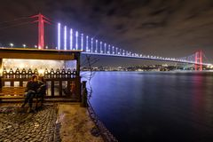 Illuminated first Bosphorus Bridge, Istanbul, Turkey at night. Nightshot of a young woman sitting on a bench with the lights of a restaurant and the first royalty free stock images