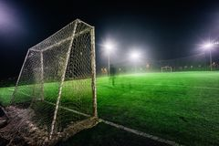 Illuminated football playground with green grass royalty free stock images