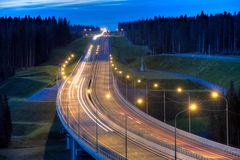 Illuminated forest highway bridge at evening with light trails. Royalty Free Stock Photography