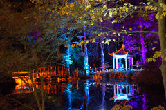 Illuminated Bridge and Forest at Night. Multi-coloured lanterns and  spotlights illuminate a wooden bridge and pagoda for the Diwali Festival of Light at Robin Royalty Free Stock Photos