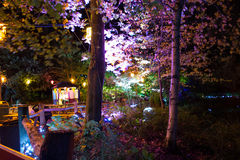 Illuminated Forest at Night. Multi-coloured lanterns and spotlights illuminate a wooden pagoda and trees for the Diwali Festival of Light at Robin Hill on the Stock Photography