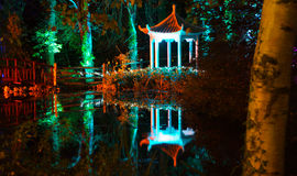 Forest Reflections at Night. Multi-coloured spotlights illuminate a pagoda and wooden bridge in The Electric Woods for a  the Diwali Festival of Light at Robin Stock Images