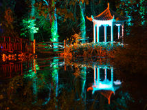 Forest, Wooden Bridge and Lake at Night. Multi-coloured spotlights illuminate a pagoda and wooden bridge in The Electric Woods for a  the Diwali Festival of Stock Image