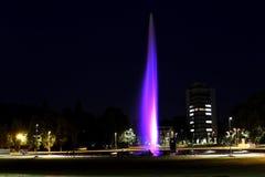 Illuminated fountain in city night scene