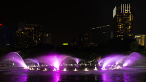 Illuminated fountain at night in modern city Stock Photos