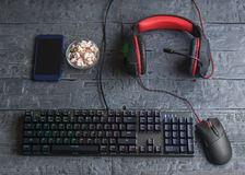 Illuminated gaming keyboard, headphones, mouse and marshmallow on a wooden table. The view from the top. Illuminated gaming keyboard, headphones, mouse and Royalty Free Stock Photography