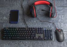 Illuminated gaming keyboard, headphones and mouse on a wooden table. The view from the top. Illuminated gaming keyboard, headphones, mouse and marshmallow on a Royalty Free Stock Photo