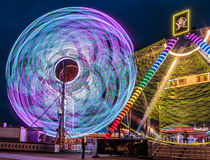 Illuminated Giant Ferris Wheel Amusement ride. Giant Ferris Wheel and Sea Ray amusement ride side by side in night time shot with long exposure Stock Photography