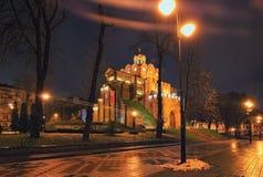 Illuminated Golden Gate and Yaroslav the Wise monument - one of the famous landmark of Kyiv at winter morning. Ukraine. Royalty Free Stock Image