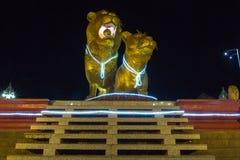 Illuminated golden lions at night, center of Sihanoukville. Camb Stock Photo