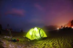 Illuminated green camping tent under stars at night Stock Photo