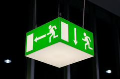 Illuminated green emergency exit sign Royalty Free Stock Images
