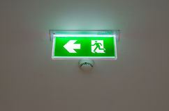 Illuminated green exit sign suspended from the ceiling Stock Photos