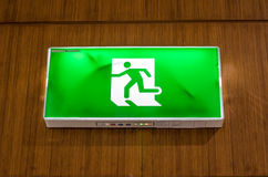 Illuminated green exit sign suspended from the ceiling Royalty Free Stock Photos