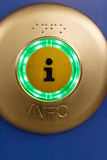 Illuminated green Information button. With a central - i - icon and the text Info below on brass over a blue background with copy space Stock Images