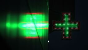 Illuminated green and red pharmacy sign at night stock video footage