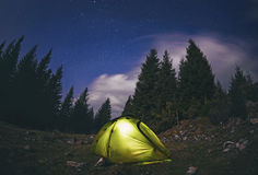Illuminated  green  tent under stars at night  forest Royalty Free Stock Photo