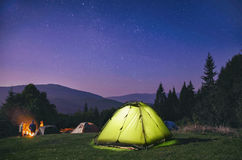 Illuminated  green  tent under stars at night  forest Stock Image