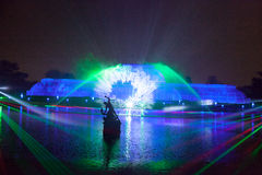 Illuminated greenhouse with digital snow flake. Lights and lasers over the lake Stock Photos
