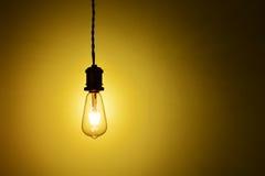 Illuminated hanging led  lamp bulb. New type hanging led lamp bulb over orange  background.three generations of light bulb such as regular incandescent lamp bulb Royalty Free Stock Image