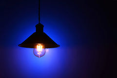 Illuminated hanging led  light bulb over blue background Royalty Free Stock Images